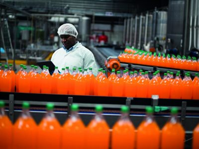 Factory engineer monitoring filled juice bottle on production line in bottle factory